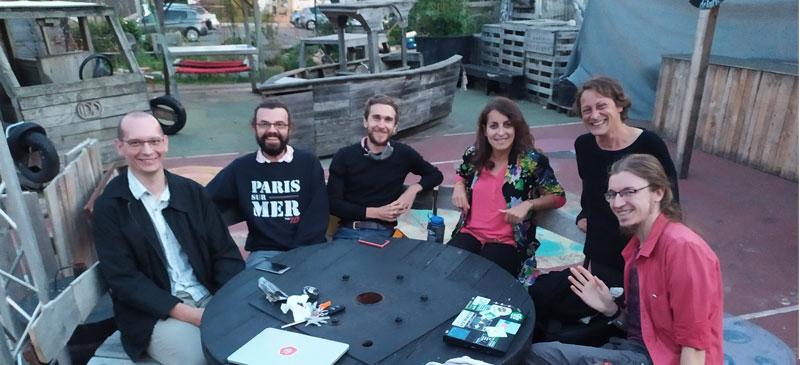 un groupe de personnes assises autour d'une table, souriant à l'objectif